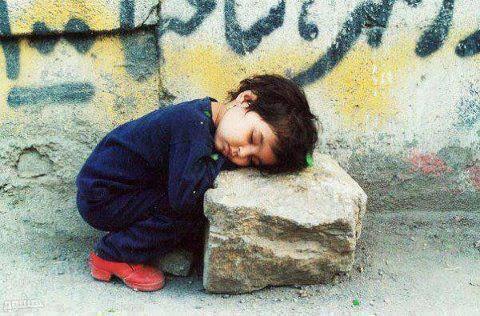 child-sleeping-on-rock